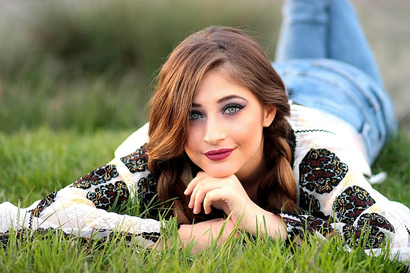 Woman in white and black top and blue jeans lying on green grass