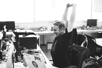 Grayscale photo of man lifting stretching sitting on chair in front of computer set