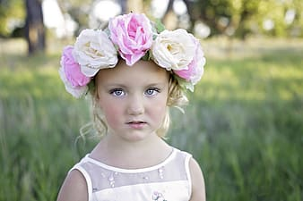 Closeup photo of girl wearing white dress and floral headband