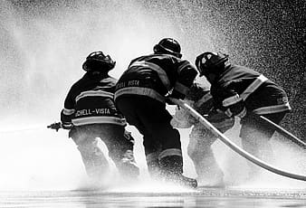 Grayscale photo of firefighter holding fire hose