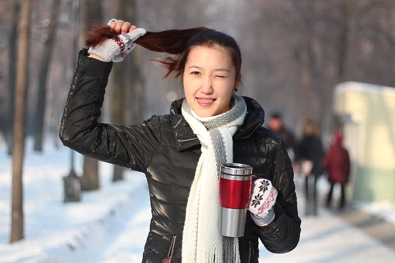 Woman holding her hair and grey mug standing on snow covered ground