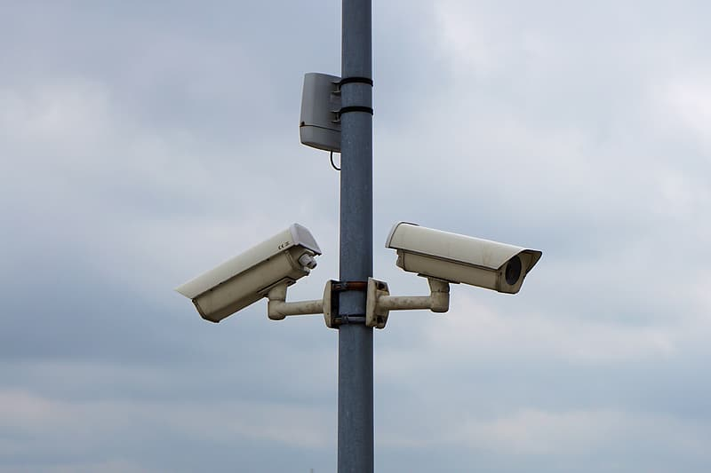 Two white bullet type security cameras