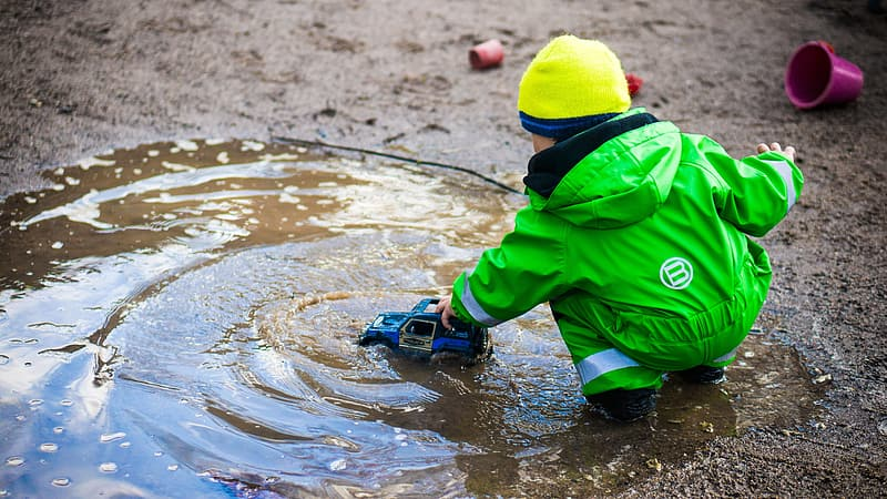 Boy wearing green hooded jumpsuit playing blue toy truck on water during daytime