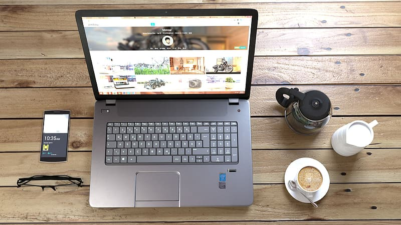 Turned on laptop computer beside coffee and turned on smartphone