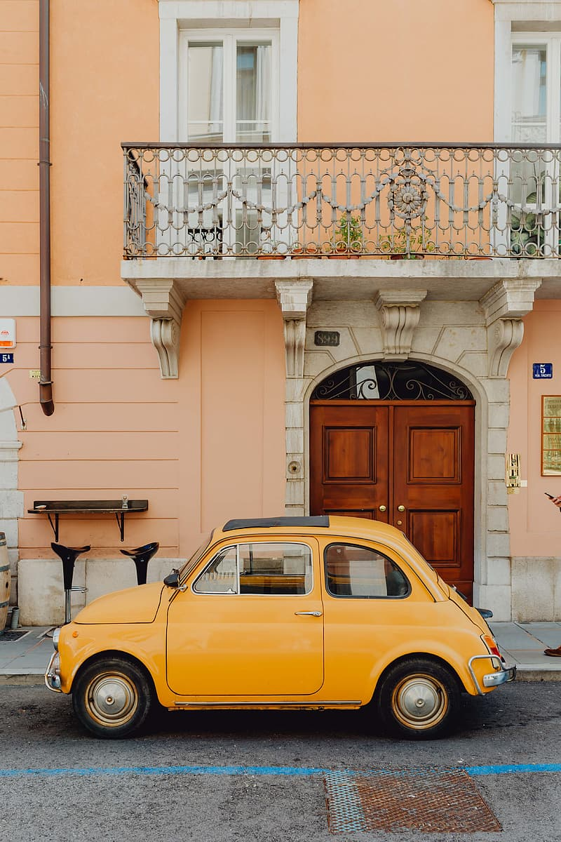 Yellow volkswagen beetle parked beside white concrete building during daytime