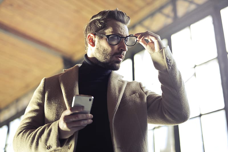 Young Adult Man removing his glasses with the right hand and holding a cellphone his left hand