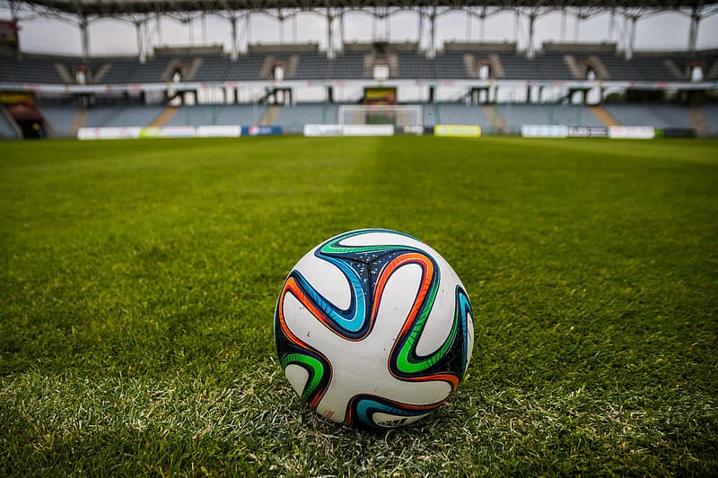 Tilt-shift lens photography of multicolored soccer ball on green grass soccer field of an empty stadium