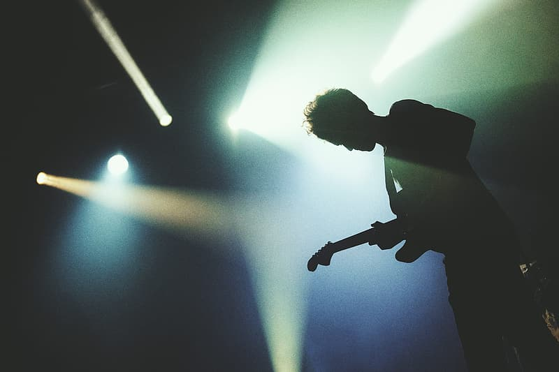 Man playing a guitar in concert lights