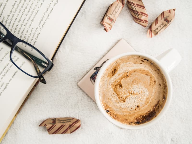 Cup of coffee beside book with black framed eyeglasses