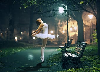 Ballerina posing in front of bench during nighttime