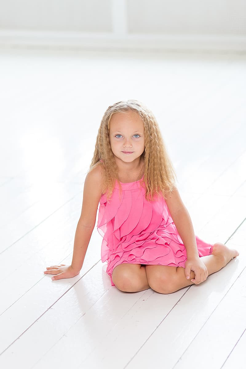 Girl wearing pink dress sitting on the floor