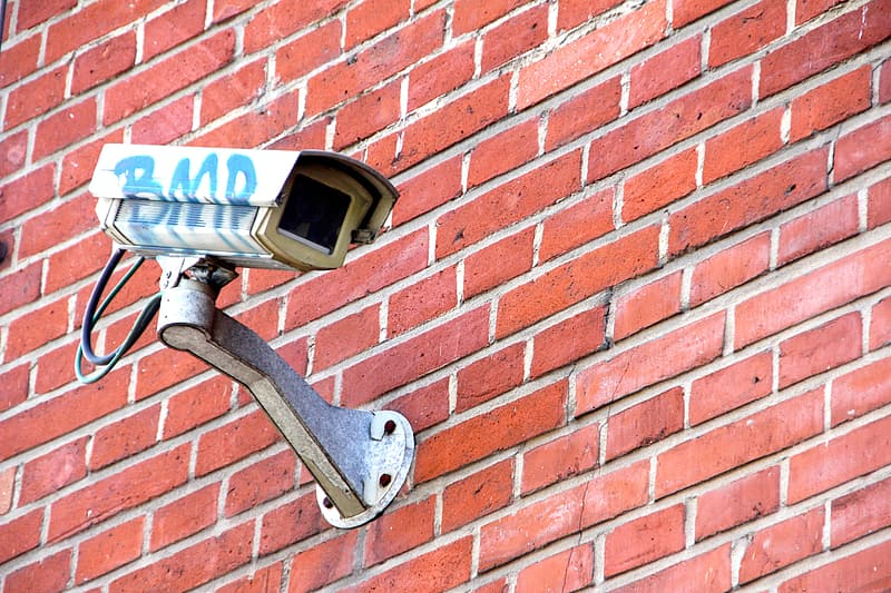 White surveillance camera on wall during daytime