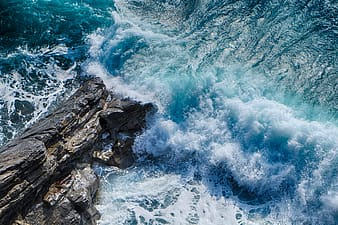Ocean waves crashing on rocky shore during daytime