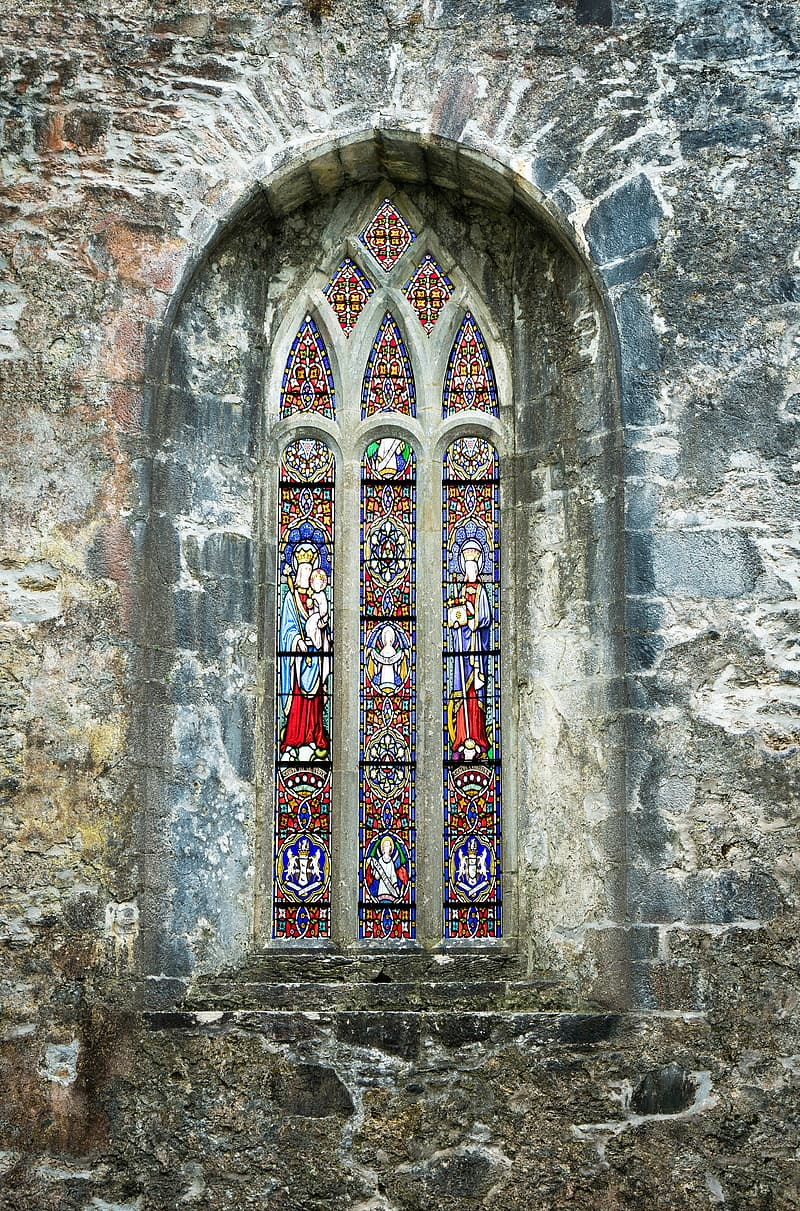 Gray and black concrete window with religious glass