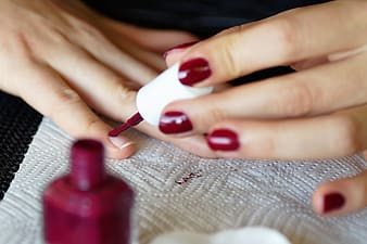 Person holding red nail polish