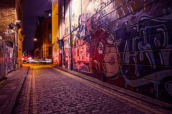 City side street with street art and graffiti captured by night