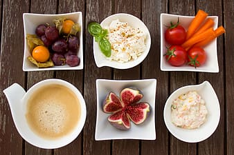 Six white ceramic bowls filled with assorted dishes