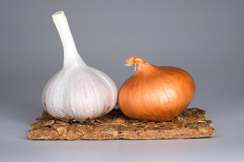 Two garlic bulb on brown wooden table