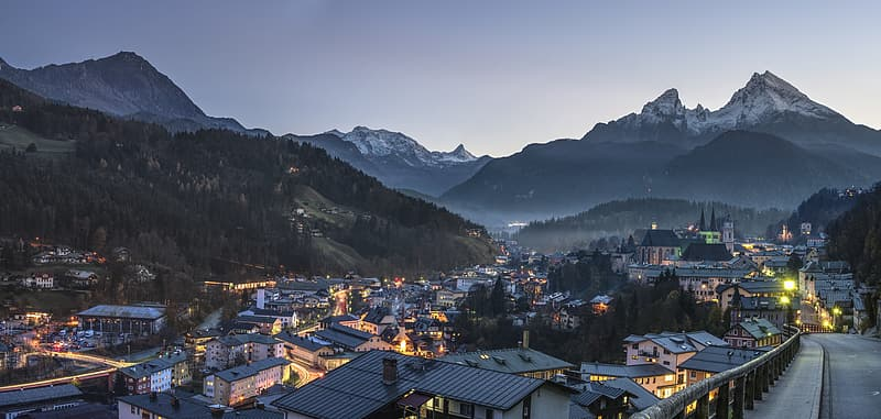 High angle photo of town buildings and mountain under dim sky