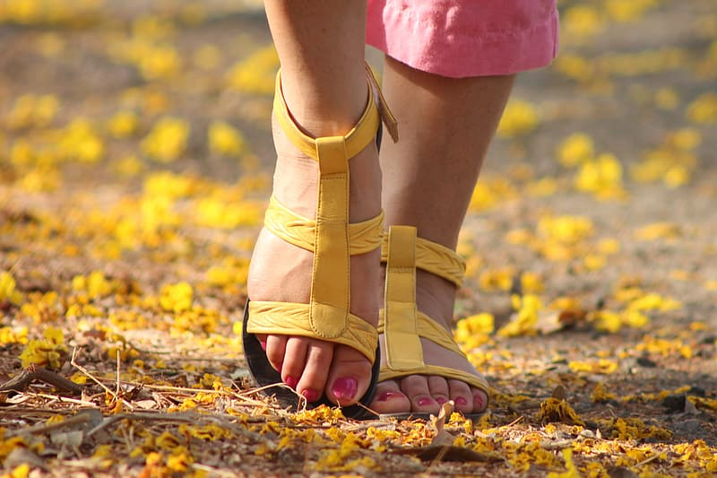 Person holding pair of yellow sandals