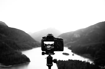 Grayscale photography of camera and mountains