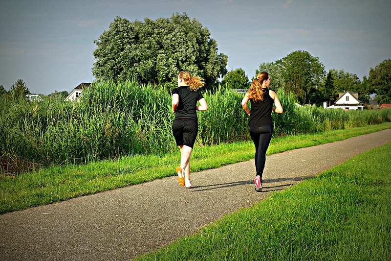 Two women in black tops and bottoms running on grey trail