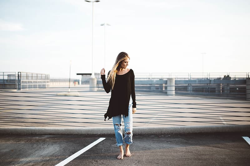 Woman wearing black long-sleeved shirt standing on grey concrete road