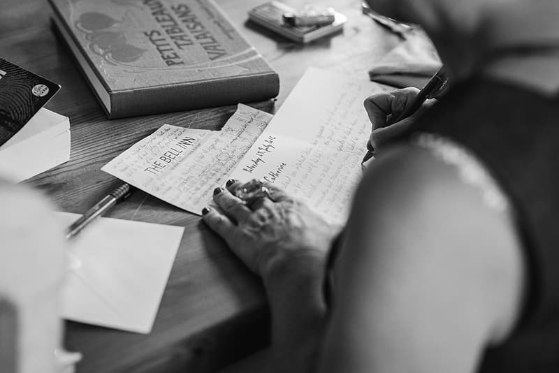 Person writing letter grayscale photo