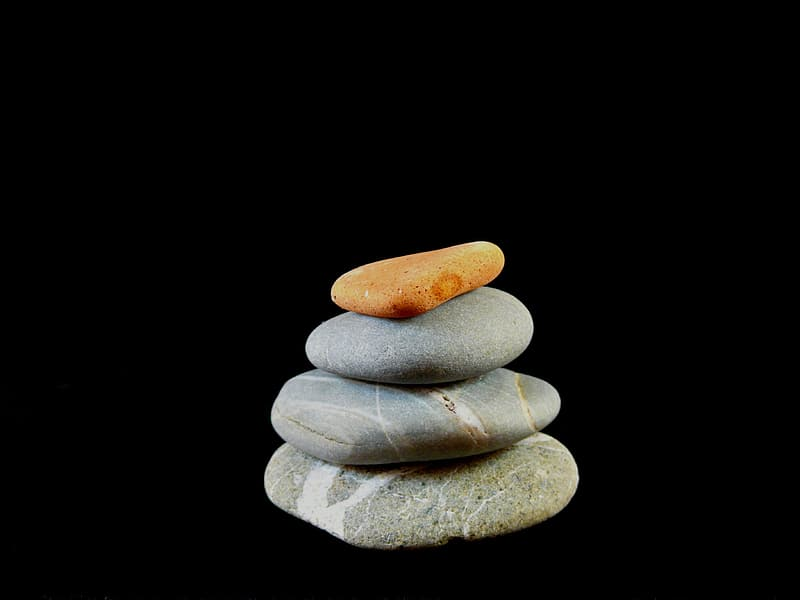 Three gray and one brown pebbles