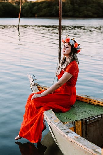 Woman in red dress sitting on white wooden boat during daytime