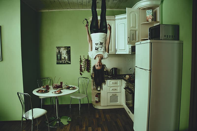Woman standing on ceiling beside white top-mount refrigerator in house