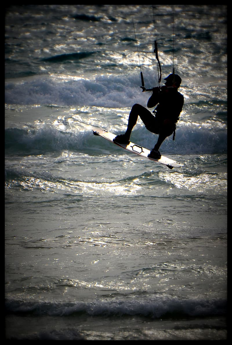 Man in black shirt and black pants surfing on sea waves during daytime