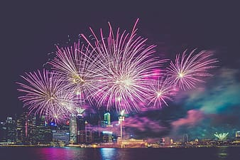 Fireworks display over city buildings during night time