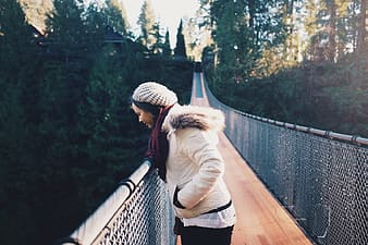 Woman in beige jacket standing on bridge during daytime