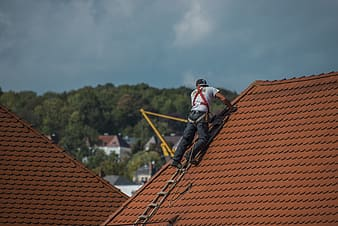 Man climbing on roof at daytime