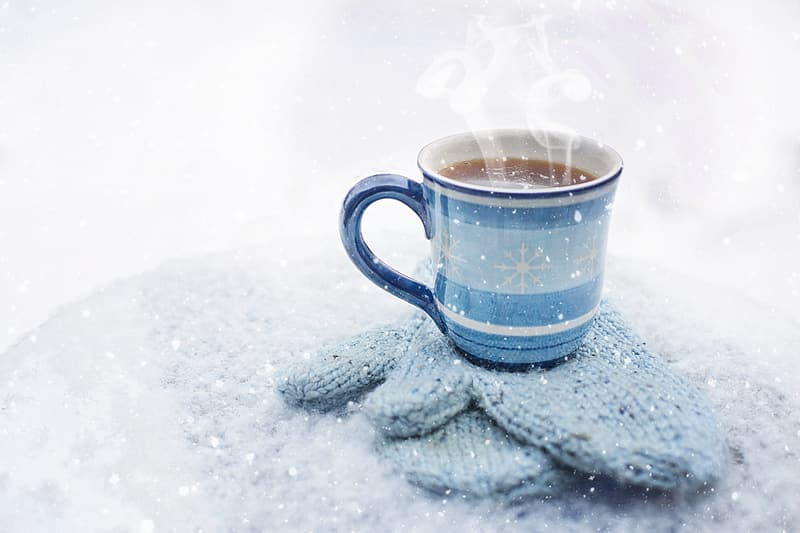 Ceramic mug on knitted gloves with hot liquid