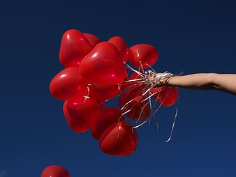 Person holding heart balloons