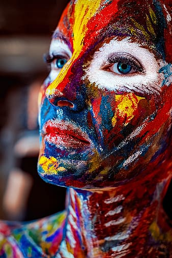 Macro photo of multicolored face painted blue-eyed woman