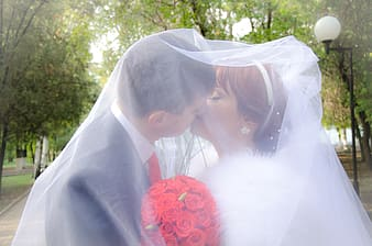 Man and woman kissing white in veil