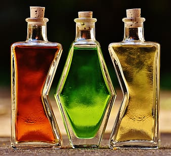 Three clear glass bottles with yellow, green, and red liquids