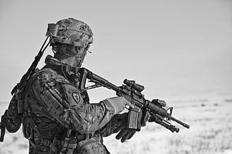 Grayscale photo of a soldier holding sniper rifle