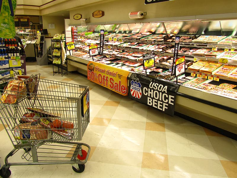 Gray shopping cart in front of display freezer