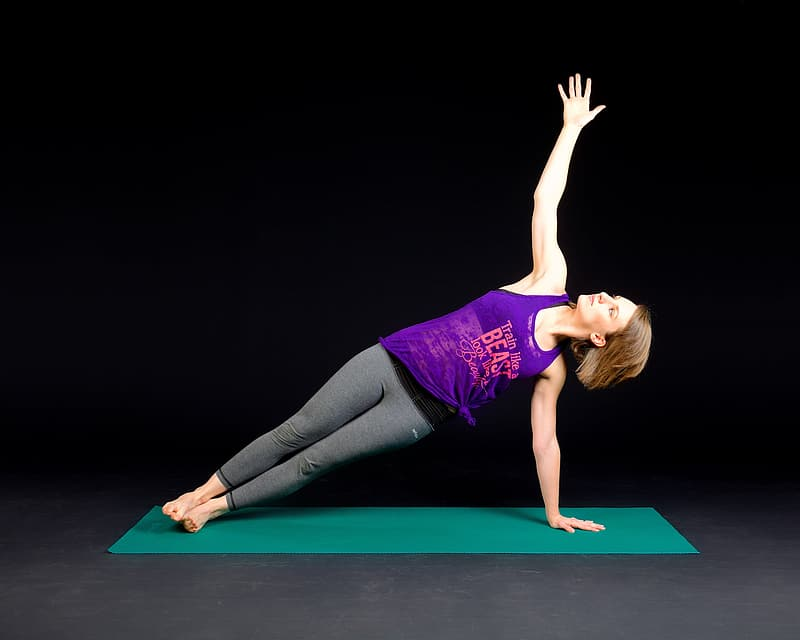 Woman wearing purple tank top and gray leggings with and yoga position on green yoga mat