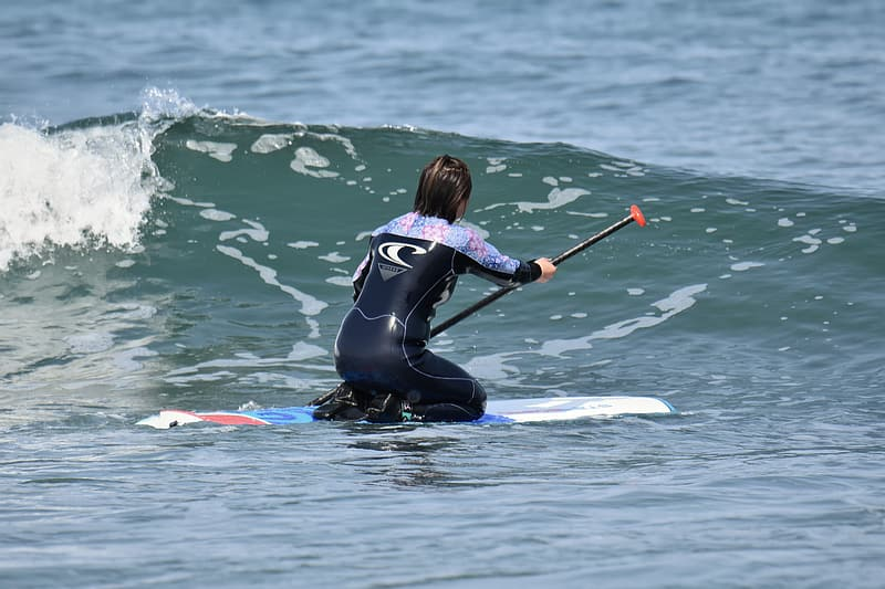 Woman in black wetsuit riding on blue and white surfboard during daytime