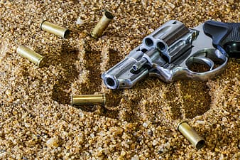 Chrome revolver pistol on brown sands