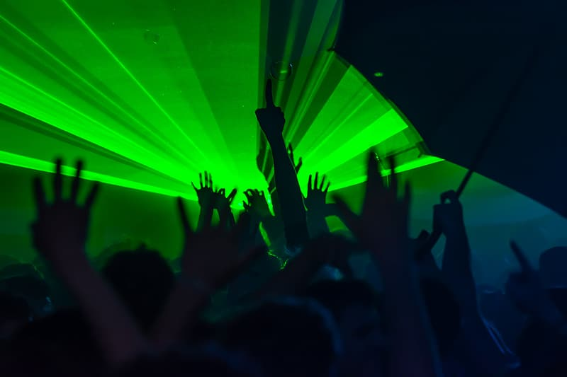 Silhouette photography of people raising hands with green light