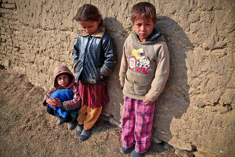 Three children leaning on brown concrete wall photo