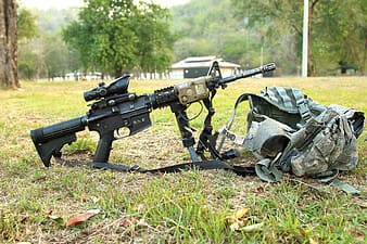 Black assault rifle with scope beside gray tactical vest on green grass field photo