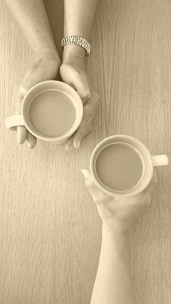 Photographed of two person holding mugs