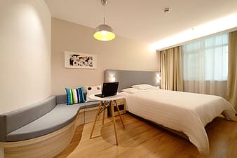 Gray bed frame beside white and brown wooden side table
